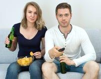 Homem e mulher que olham a tevê foto de stock royalty free
