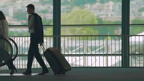 Homem e mulher que pisam na escada rolante para montar para baixo, mala de viagem levando do indivíduo, serviço vídeos de arquivo