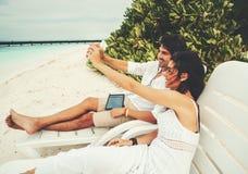Homem e mulher que refrigeram em cadeiras de praia Fotos de Stock