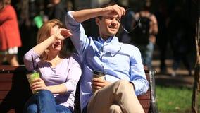 Homem e mulher que sentam-se em um banco Um homem e uma mulher bonita em uma data Bebem o café e falam video estoque