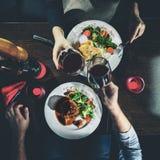 Homem e mulher que têm o jantar romântico em um restaurante, imag tonificado fotografia de stock