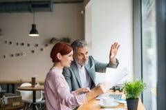 Homem e mulher que têm a reunião de negócios em um café, usando o portátil imagens de stock