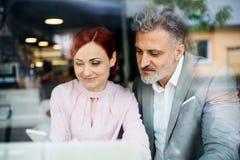 Homem e mulher que têm a reunião de negócios em um café, usando o smartphone imagens de stock