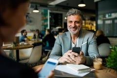 Homem e mulher que têm a reunião de negócios em um café, usando smartphones imagem de stock