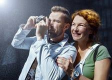 Homem e mulher que tomam a imagem na câmera do vintage, dia, exterior Fotos de Stock