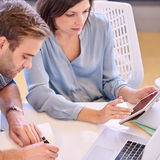 Homem e mulher que trabalham junto proximamente no trabalho no escritório Fotos de Stock Royalty Free