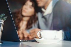 Homem e mulher que trabalham na frente do portátil O copo de chá está no primeiro plano imagem de stock royalty free