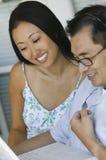Homem e mulher que usa o portátil e os auriculares Imagem de Stock Royalty Free
