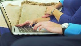 Homem e mulher que usa o portátil no sofá vídeos de arquivo