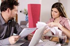 Homem e mulher que verificam as contas em casa preocupadas Imagens de Stock Royalty Free