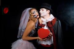 Homem e mulher que vestem como o vampiro e a bruxa. Dia das bruxas imagem de stock