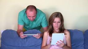 Homem e mulher sérios que usa o tablet pc no sofá em casa closeup vídeos de arquivo