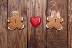 Homem e mulheres de pão-de-espécie com um coração no fundo de madeira Coração verde estilizado da ilustração do vetor Imagem de Stock Royalty Free