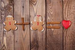 Homem e mulheres de pão-de-espécie com um coração no fundo de madeira Coração verde estilizado da ilustração do vetor Foto de Stock
