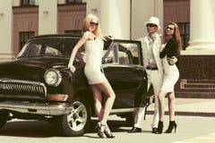 Homem e mulheres novos felizes da forma ao lado de um carro do vintage Imagem de Stock