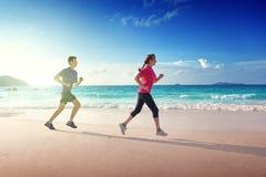 Homem e mulheres que correm na praia tropical Fotografia de Stock Royalty Free