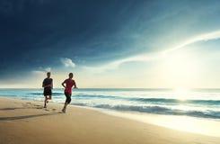 Homem e mulheres que correm na praia tropical Fotografia de Stock
