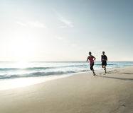 Homem e mulheres que correm na praia tropical no por do sol Foto de Stock Royalty Free