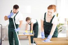 Homem e mulheres que limpam a casa fotografia de stock royalty free