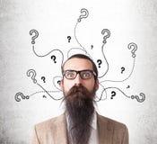 Homem e pontos de interrogação confundidos no muro de cimento Foto de Stock