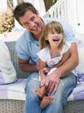 Homem e rapariga que sentam-se no riso do pátio fotografia de stock royalty free