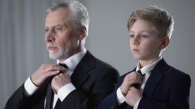 Homem e rapaz pequeno adultos nos ternos de negócio que ajustam laços, sucessor futuro filme
