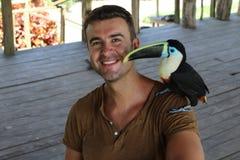 Homem e seu pássaro domesticado do tucano fotografia de stock