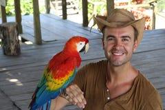 Homem e seu papagaio domesticado foto de stock