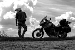 Homem e turista do motociclista fora da motocicleta da estrada com o cavaleiro do homem novo de sacos laterais a descansar durant foto de stock