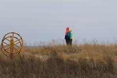 Homem e uma mulher em um monte com a grama alta que olha afastado pensativamente fotografia de stock