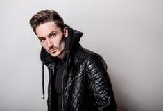 Homem elegante atrativo no casaco de cabedal preto à moda que levanta na luz - fundo cinzento fotos de stock