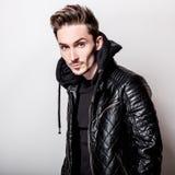 Homem elegante atrativo no casaco de cabedal preto à moda que levanta na luz - fundo cinzento foto de stock