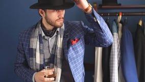 Homem elegante no terno da forma e chapéu que levanta na oficina com bebida video estoque