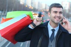 Homem elegante que guarda os sacos de compras que chamam pelo telefone Fotografia de Stock