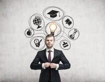 Homem em ícones do terno e da educação no concreto Imagem de Stock