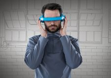 Homem em auriculares azuis da realidade virtual contra mão cinzenta janelas tiradas Fotos de Stock