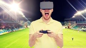 Homem em auriculares da realidade virtual sobre o campo de futebol Fotografia de Stock Royalty Free