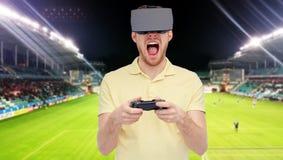 Homem em auriculares da realidade virtual sobre o campo de futebol Fotos de Stock