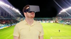 Homem em auriculares da realidade virtual sobre o campo de futebol Fotografia de Stock