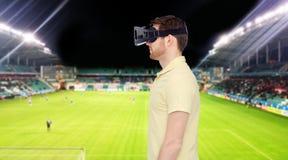 Homem em auriculares da realidade virtual sobre o campo de futebol Imagens de Stock