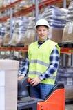 Homem em caixas da carga da empilhadeira no armazém Fotos de Stock