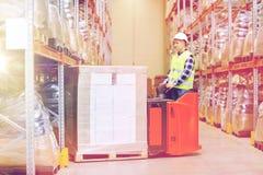 Homem em caixas da carga da empilhadeira no armazém Imagens de Stock
