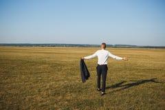 Homem em calças pretas e na camisa branca com o revestimento nas mãos Simboliza a liberdade de escolha após a destituição do trab foto de stock
