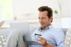 Homem em casa que compra no Internet fotos de stock
