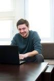 Homem em casa que trabalha em um portátil Foto de Stock