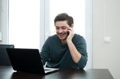 Homem em casa que trabalha em um portátil Fotos de Stock