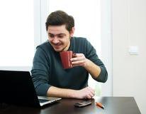 Homem em casa que trabalha em um portátil Imagens de Stock