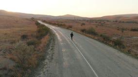 Homem em corridas do terno na estrada vazia filme