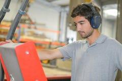 Homem em defensores de orelha vestindo da fábrica imagem de stock