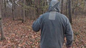Homem em Dia das Bruxas assustador que olha no parque e que anda afastado video estoque